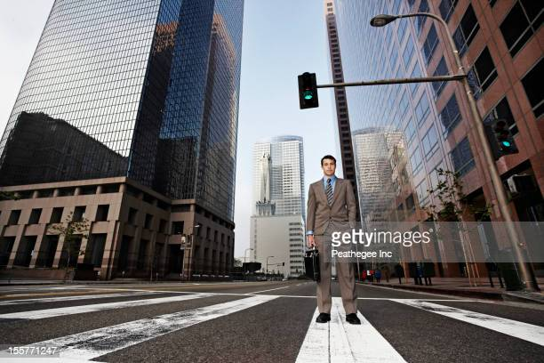 Businessman standing in urban crosswalk