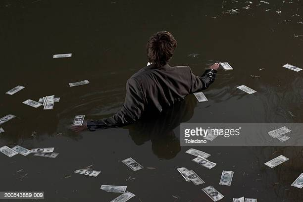 Businessman standing in water surrounded by bundles on banknotes