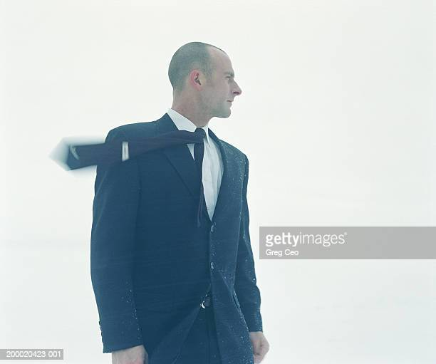 Businessman standing in wind (blurred motion)