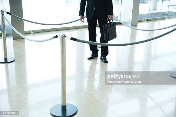 Businessman standing inside roped off area in lobby