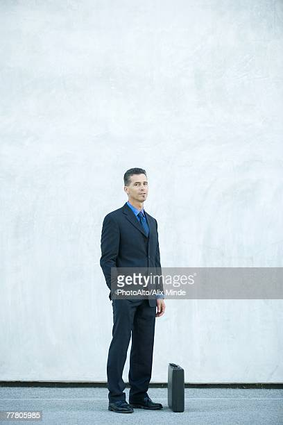 Businessman standing, looking at camera, full length portrait