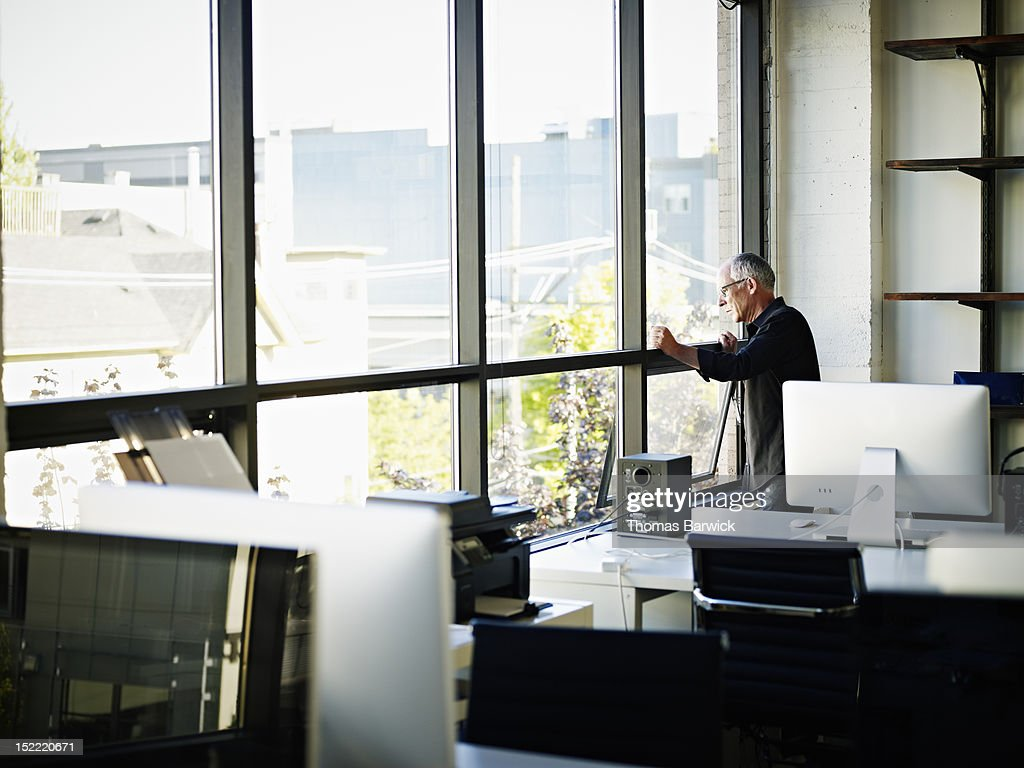 Businessman standing looking out window in office : Stock Photo