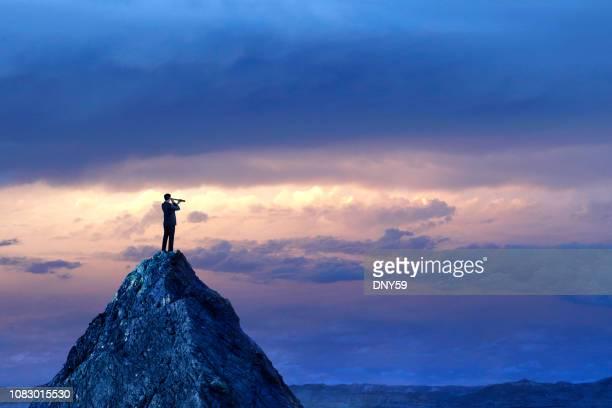 empresário em pé olhando pela luneta no pico da montanha - conveniência - fotografias e filmes do acervo
