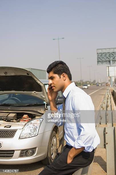 Businessman standing near a broken down car and talking on a mobile phone, Gurgaon, Haryana, India