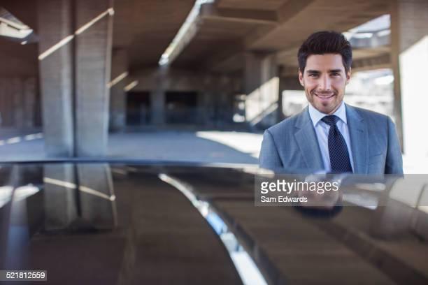 Businessman standing near car in parking garage