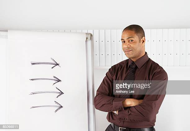 Businessman standing near flip chart with drawings of arrows