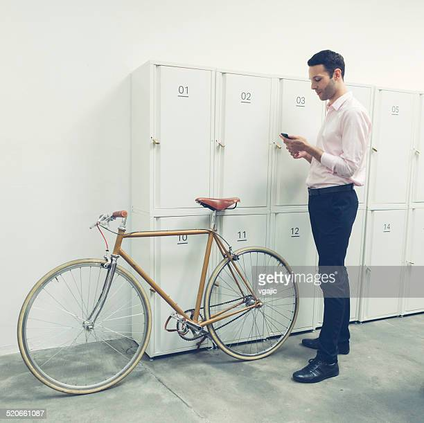 Businessman standing near lockers and texting.