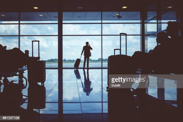 Businessman standing near window in airport using mobile phone