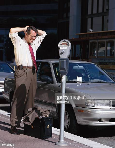 businessman standing next to a parking meter with his hand on his head - parking meter stock photos and pictures
