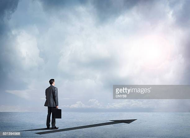 Businessman Standing Next To Arrow Pointing Into Distance
