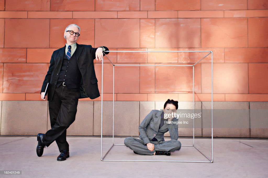 Businessman standing next to co-worker in box : Stock Photo