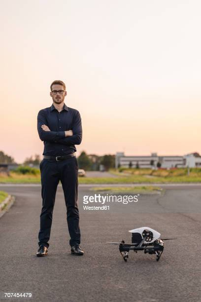 Businessman standing next to drone