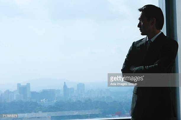 Businessman standing next to window, looking out