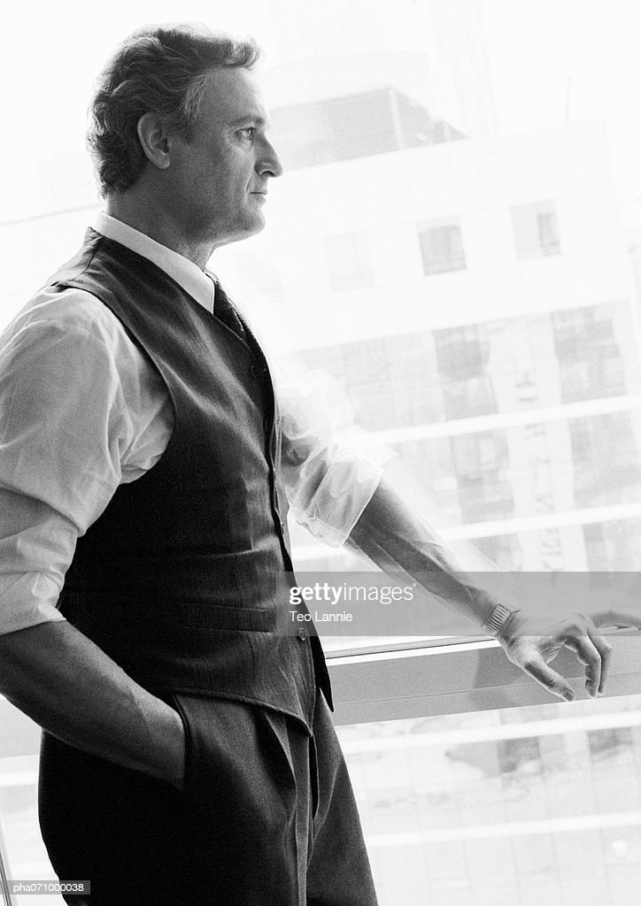 Businessman standing next to window looking out, side view, b&w. : Stockfoto