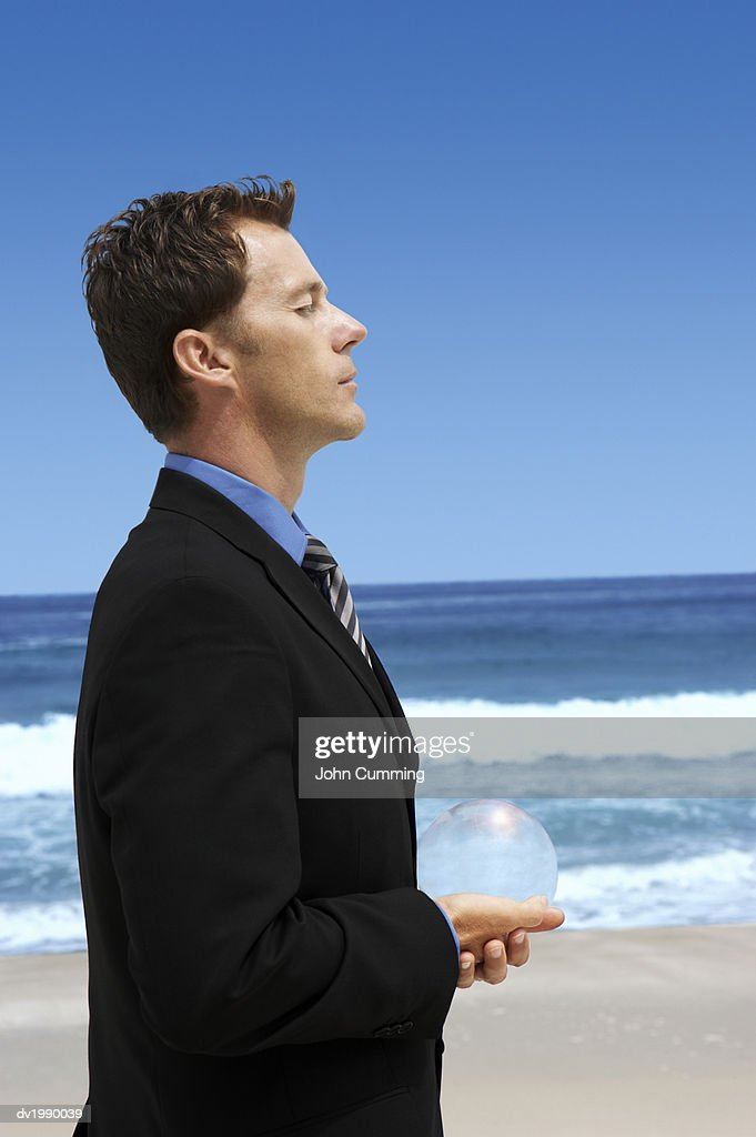 Businessman Standing on a Beach and Holding a Sphere in His Cupped Hands : Stock Photo