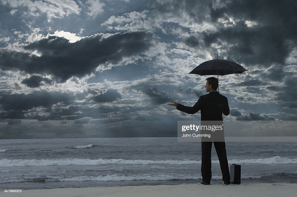 Businessman Standing on a Beach at Night, Holding an Umbrella and Checking for Rain : Stock Photo