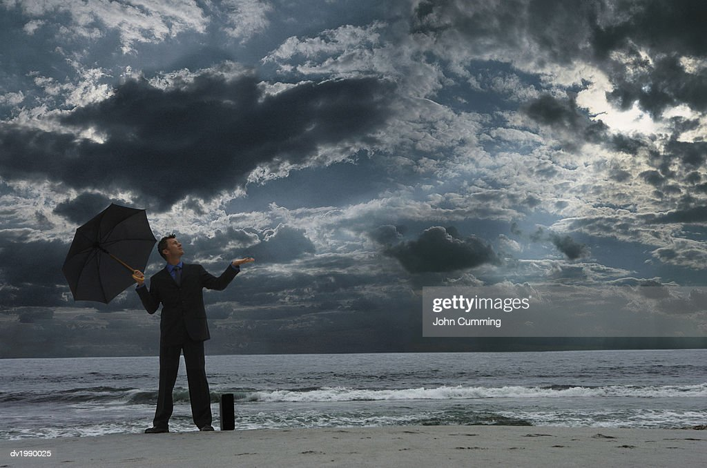 Businessman Standing on a Beach at Night, Looking Up From  an Umbrella and Checking for Rain : Stock Photo