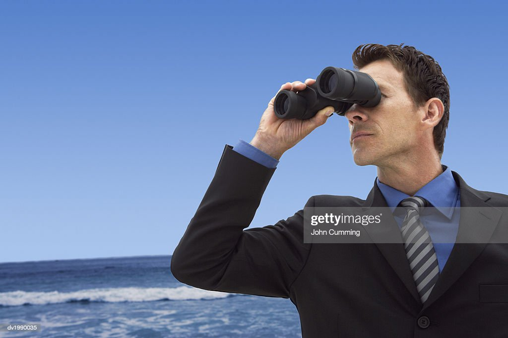Businessman Standing on a Beach Looking Through Binoculars : Stock Photo