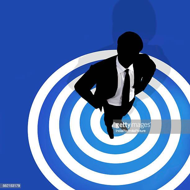 Businessman standing on a bulls eye