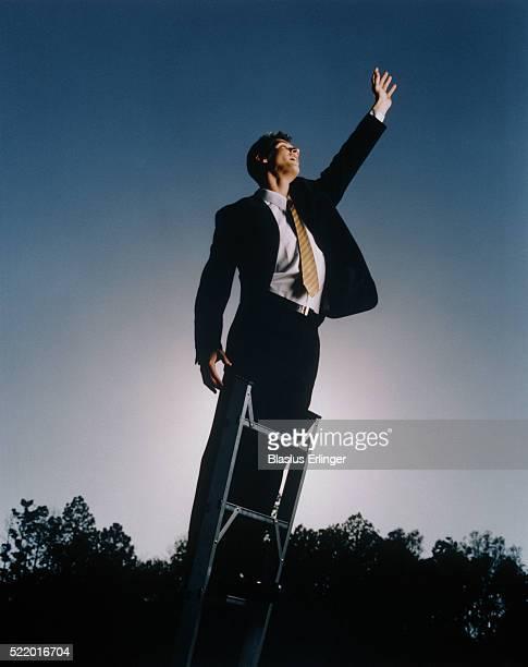 Businessman standing on a ladder, raising hand