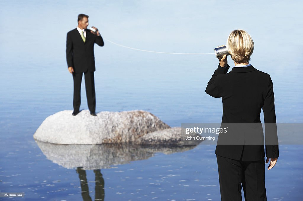 Businessman Standing on a Rock in the Sea, Talking to a Businesswoman Through Two Tin Cans Connected by String : Stock Photo