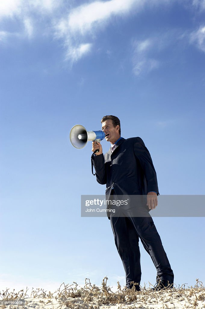 Businessman Standing on a Sand Dune and Shouting Into a Megaphone : Stock Photo