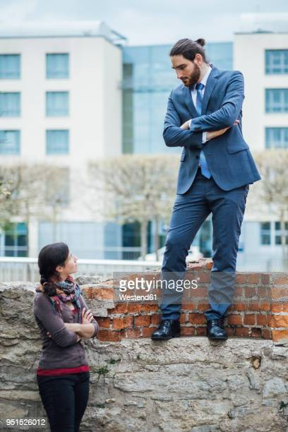 Businessman standing on a wall looking down at woman