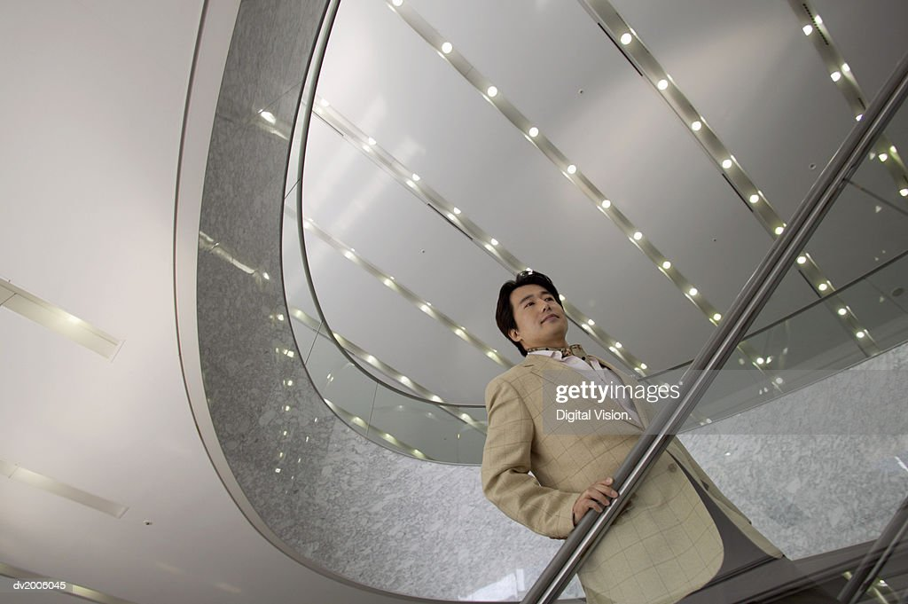Businessman Standing on an Escalator : Stock Photo