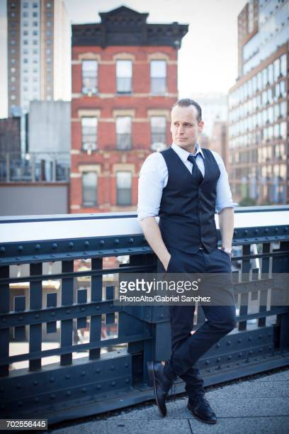 Businessman standing on balcony, looking away in thought