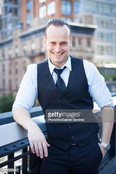Businessman standing on balcony, smiling, portrait