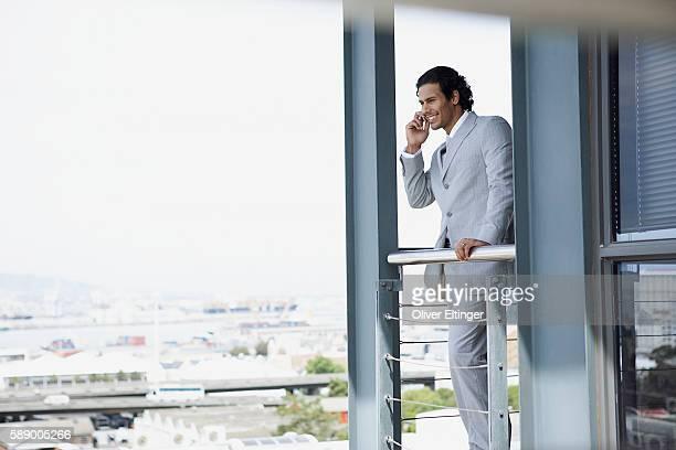 businessman standing on balcony using cell phone - oliver eltinger stock-fotos und bilder