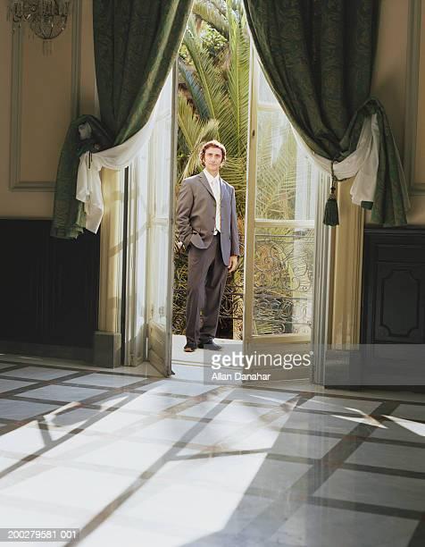 Businessman standing on balcony, view through doorway, portrait