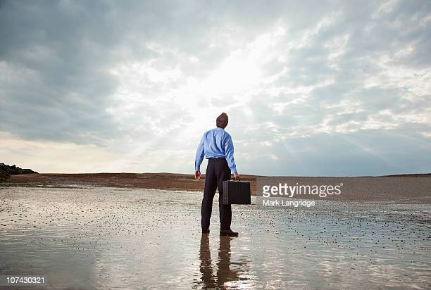 Businessman standing on beach looking at sky