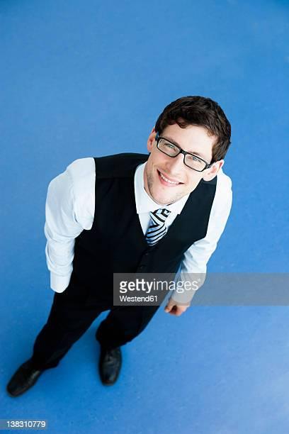 Businessman standing on blue background, smiling, portrait