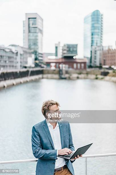 Businessman standing on bridge using laptop