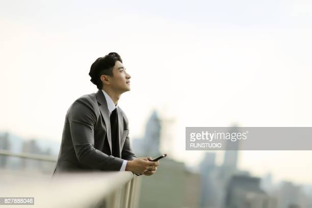 businessman standing on city rooftop - asia stock pictures, royalty-free photos & images