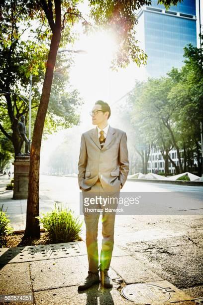 Businessman standing on city sidewalk