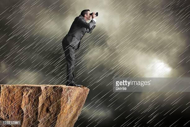 Businessman standing on cliff in driving rain looking through binoculars