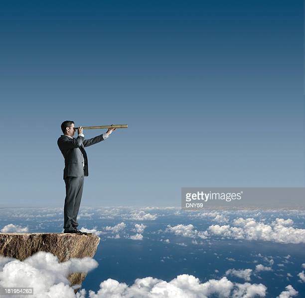 Businessman Standing On Cliff Looking Through Spyglass