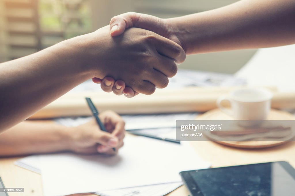 Businessman standing on coin and  Shake hand each other with Smartphone and expensive pen to sign deal : Stock Photo