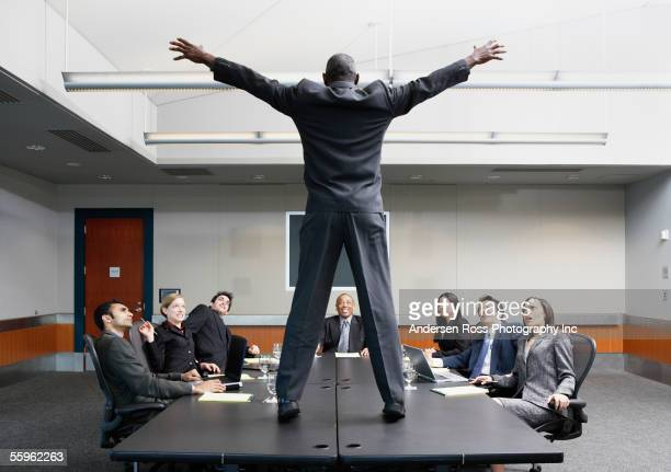 businessman standing on conference table - shock tactics stock pictures, royalty-free photos & images