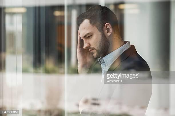 Businessman standing on glass pane, hand on head