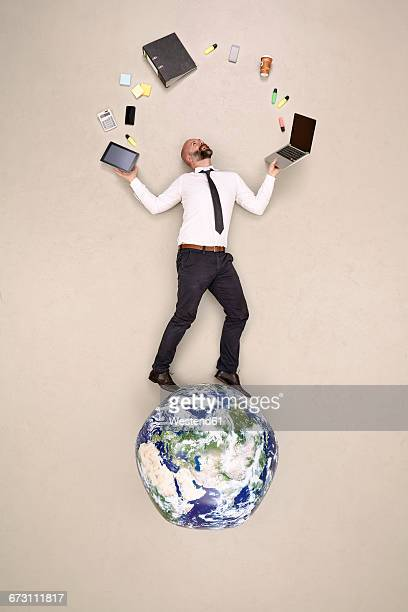 Businessman standing on globe juggling with office devices