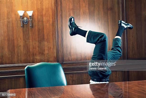businessman standing on head in boardroom - auf den kopf gestellt stock-fotos und bilder