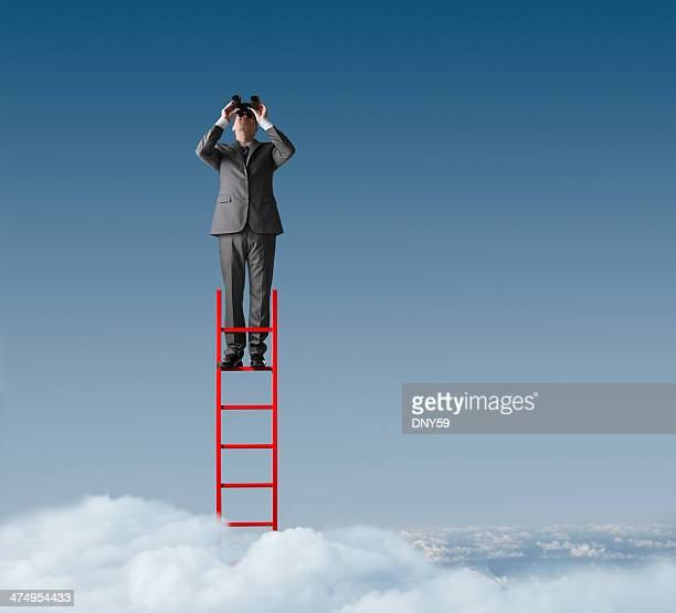 Businessman standing on ladder looking through binoculars