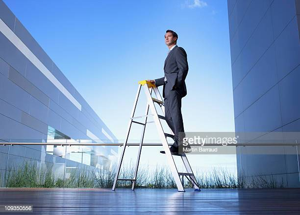 Businessman standing on ladder on balcony