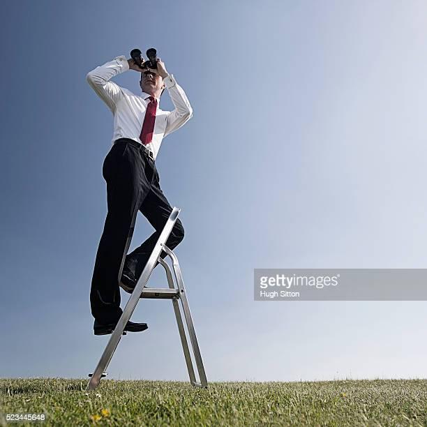 businessman standing on ladder using binoculars outdoors - hugh sitton bildbanksfoton och bilder