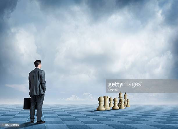 businessman standing on large chessboard looks towards chess pieces - tabuleiro de xadrez imagens e fotografias de stock