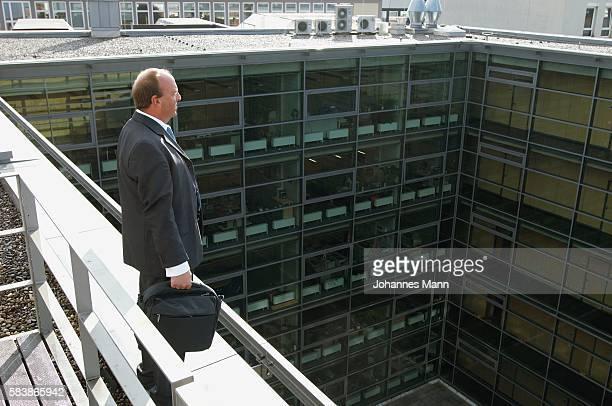 businessman standing on ledge - suicidio foto e immagini stock