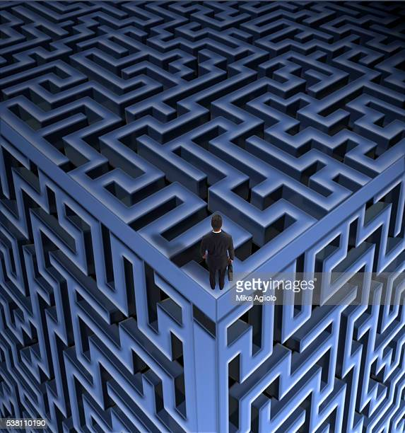 businessman standing on maze cube - mike agliolo stock photos and pictures